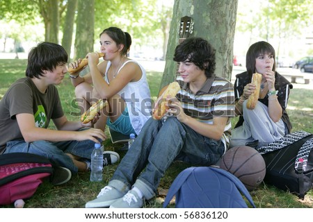 Teenagers sitting in the grass eating sandwiches - stock photo