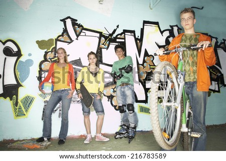 Teenagers standing against a wall. - stock photo