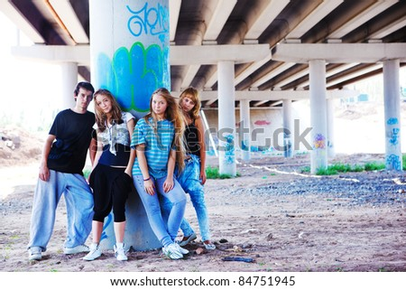 Teenagers standing at the column marked with graffiti - stock photo