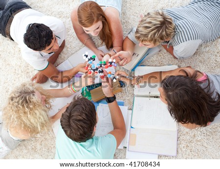 Teenagers studying Science on the floor in a house - stock photo