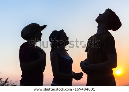 Teenagers Talk Silhouettes Teenagers girls and boy talk laugh silhouetted against setting sun - stock photo