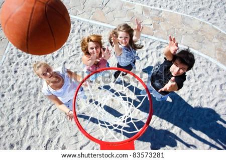 Teenagers team playing street basketball
