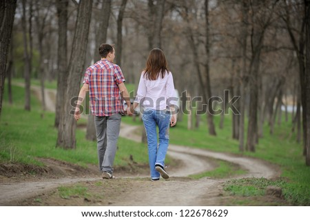teenagers walking away along forest path - stock photo