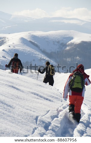 Teenagers walking on a new path through snow in the mountains - stock photo