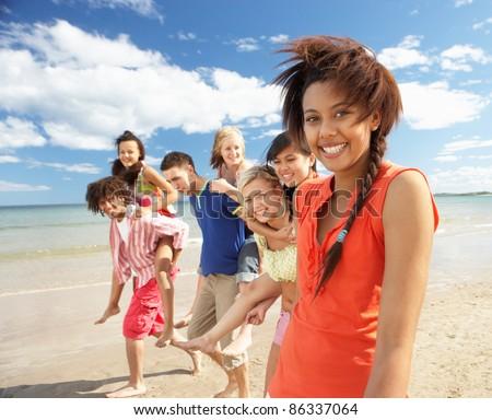 Teenagers walking on beach - stock photo