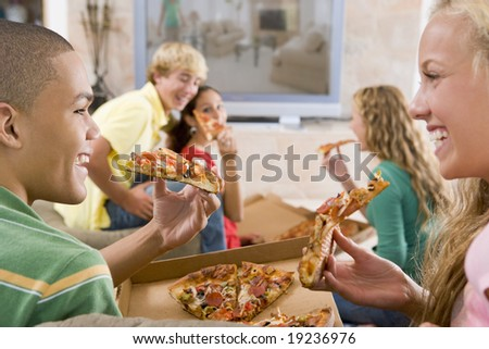 Teenagers Watching TV And Eating Pizza - stock photo