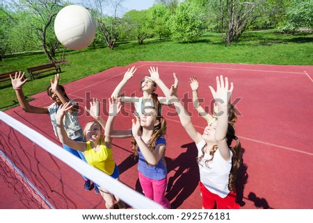 Teenagers with arms up are playing volleyball - stock photo