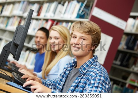 Teenagers working on computers in library - stock photo
