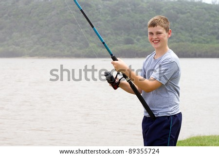 teengae boy fishing by the river - stock photo