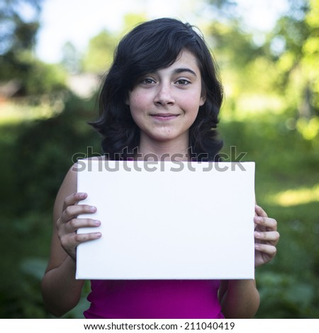 Teengirl holding clean white sheet paper, outdoors (banner for your message) - stock photo