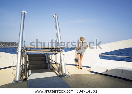 Teennager girl looks at the sea from the deck of a boat - stock photo