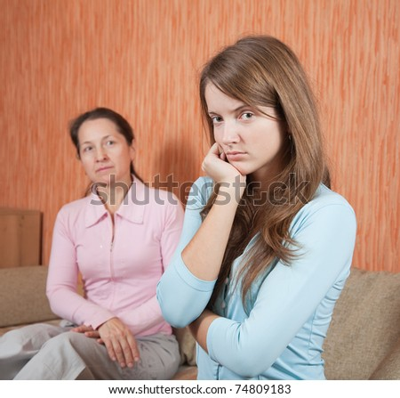 teenr daughter and mature mother having quarrel at home - stock photo