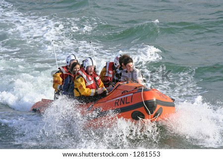 Teens being rescued by coastguards - stock photo