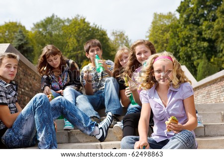 Teens eating sandwiches - stock photo