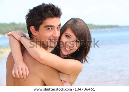 Teens embracing on the beach - stock photo