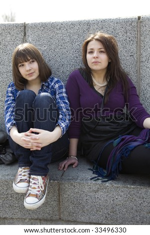 teens girl waiting and sitting on embankment