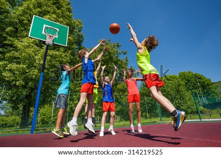 Teens in jump playing basketball game together - stock photo
