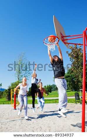 Teens jumping to get basketball hoop