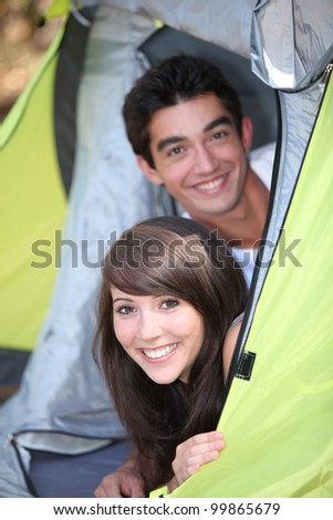 Teens leaning in tent - stock photo
