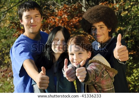 Teens of various ethnic backgrounds outdoors giving a thumbs up. Focus on teen girl second from right. - stock photo