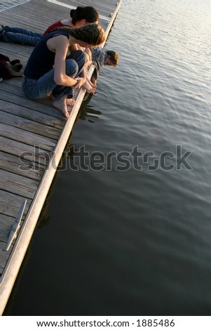 Teens on a Pier - Relaxing time at sunset - stock photo