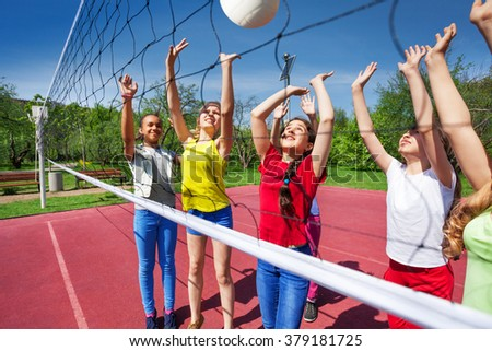 Teens playing actively near the volleyball net - stock photo
