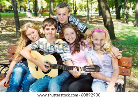 Teens playing guitar and singing - stock photo
