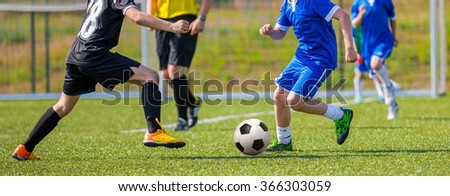 Teens Playing Soccer Football Match. Competition between two youth soccer teams. Boys in blue and black sport uniforms running and kicking soccer ball on a pitch. Football soccer tournament. - stock photo