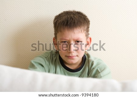 Teens problem. Sad young teenager sitting close to the wall and look out from the sofa - stock photo