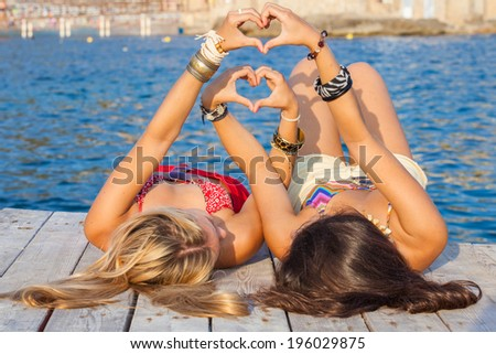 teens sign hearts for summer vacation or holiday - stock photo