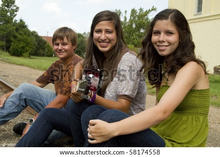 Teens sitting on railroad tracks listening to a friend play guitar music stop and smile for the camera. - stock photo