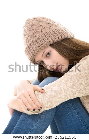 Teens troubles. Unhappy teenage girl sitting clasping her knees, looking down - stock photo