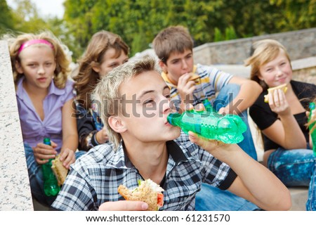 Teens with  sandwiches and soda water - stock photo