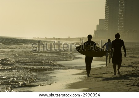 Teens with surfboards on the beach of Gulf of Mexico during school break - stock photo