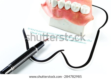 Teeth mock up model put beside the teeth check up sheet with pen represent the oral care concept related idea. Super macro shot and intention focus at the ball pen head. - stock photo