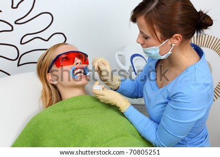 Teeth whitening. Pro at work with her pacient. - stock photo