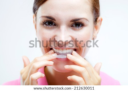 Teeth whitening, woman with tooth tray on teeth - stock photo