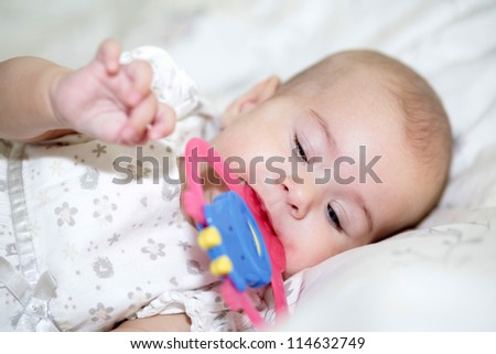 Teething baby holding toy in mouth - stock photo