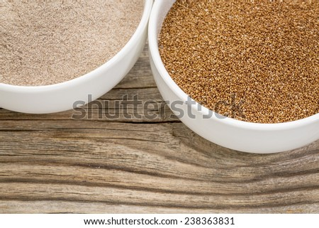 teff grain and flour in small ceramic bowls against grained wood background - stock photo