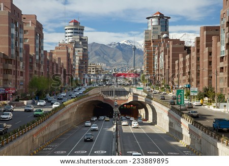 TEHRAN - APR 1: Cars Passing Through Tohid Tunnel with Milad Tower and Alborz Mountains in Background on April 1, 2014 in Tehran, Iran. Tohid Tunnel is the third longest urban tunnel in Middle East. - stock photo