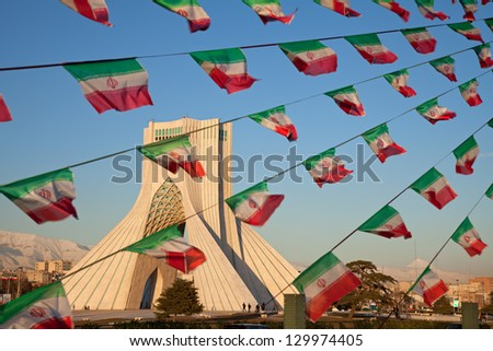 TEHRAN - FEBRUARY 11: Azadi Monument and small Iran flags on February 11, 2012 in Tehran. Anniversary of Islamic Revolution is annually celebrated in Azadi sq. and everywhere is decorated with flags. - stock photo