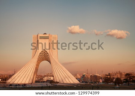 TEHRAN - FEBRUARY 11: Azadi Monument with a warm color cast during sunset on February 11, 2012 in Tehran. Azadi Monument is the most famous landmark of Tehran. - stock photo