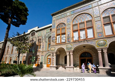 TEHRAN, IRAN - OCT 6: Crowd of tourists come from the bright persian Golestan Palace and walk to the garden on October 6, 2014. UNESCO World Heritage Site, Golestan Palace was built in 16 century.  - stock photo