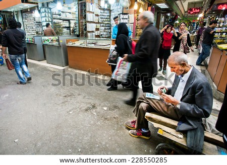 TEHRAN, IRAN - OCTOBER 6: Older serious worker of oriental market earned some money and counts the bills on October 6 2014.  - stock photo