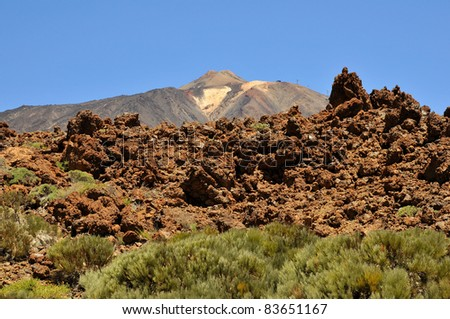 Teide volcano (Pico del Teide) in the background with blocks of lava at Tenerife in the Spanish Canary Islands - stock photo