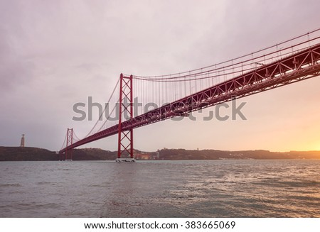 Tejo river view of Ponte 25 de Abril bridge across the Tagus river linking the cities of Lisbon and Almada, alongside with Christ the King monument, during colorful sunset. Lisboa city, Portugal. - stock photo
