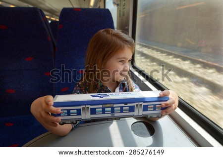 TEL AVIV - APR 05 2015:Little girl (talya Ben-Ari age 05) hold a model of Israel Railways train.It's state-owned railway company responsible for all inter-city, commuter and rail transport in Israel - stock photo