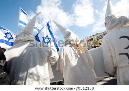 TEL AVIV - DECEMBER 9: Israeli activists dress as KKK members to satirize right-wing Israeli policies and politicians during in the annual human rights march in Tel Aviv on Dec 9, 2011.