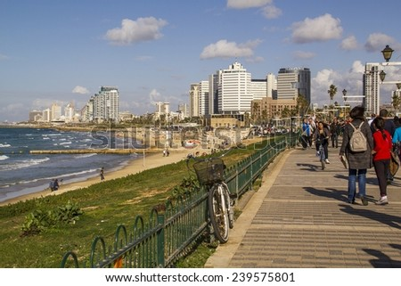 Tel Aviv,Israel-December 20,2014:Coast beach with promenade on the background of the city.Tourists and locals are enjoying a sunny day along the Tel Aviv promenade on December 20,2014 .Israel - stock photo