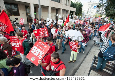 TEL AVIV, ISRAEL - DECEMBER 7: Members of the leftist Israeli political party Hadash march in red during the annual human rights march in Tel Aviv, Israel, December 7, 2012. - stock photo